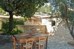 """All'aperto, fra le due case, una piccola cucina comune, una zona pranzo e una """"di conversazione"""" realizzata con sedute di muratura sormontate da lastre di pietra."""