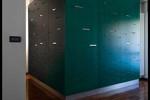 Il volume verde, da un lato è una libreria a tutta altezza in mensole in acciaio, dall'altro, caratterizza la zona d'ingresso con un sapiente gioco di illuminazione artificiale.