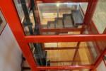 Protagonista dell'ambiente è l'arancio dell'elevatore che domina sul bianco della cucina.