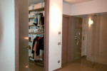 La porta che divide la stanza dalla cabina armadio è in vetro a tutta altezza