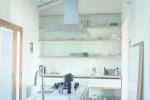 Il piano di lavoro della cucina è stato realizzato  in opera. Mensole, ripiani  e credenza, nella loro semplicità di linee  e materiali, sono stati realizzati su misura  dal falegname.