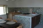 Le antiche piastrelle che rivestono parti della cucina sono enfatizzate dalle pareti interne di mattoni intonacate in bianco. Anche il tetto, in legno, trattato a calce, riproduce l'effetto grigio invecchiato