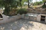 """All'aperto, fra le due case, una piccola cucina comune, una zona pranzo e una di """"conversazione"""" realizzata con sedute di muratura sormontate da lastre di pietra"""
