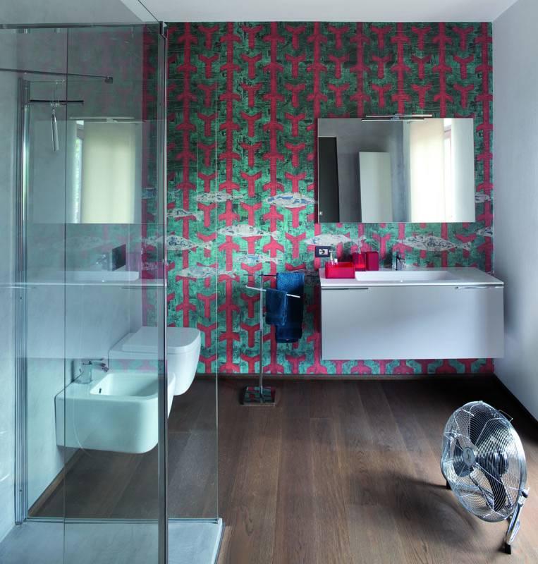 Essenziale ma molto caratteristico anche il secondo bagno dell'appartamento di Lodi, dove la parete rivestita con carta da parati sembra assorbire e poi rimandare all'esterno tutta la luce. Il motivo dei pesci e delle fantasie geometriche si bilancia in piena armonia con il resto del locale.