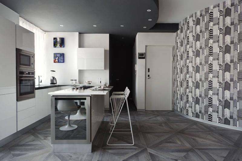 Sul lato corto dell'isola della cucina è integrata la cantinetta. In prossimità dell'ingresso la parete curva di confine, personalizzata con l'originale carta da parati.