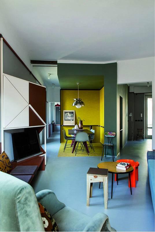 """La zona pranzo """"privata"""" si affaccia sulla zona """"pubblica"""" del salotto. Un angolo intimo ben distinto senza l'uso di pareti, ma dal sapiente uso di colori e volumi."""