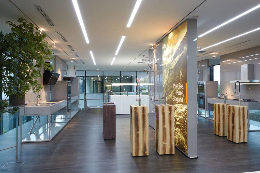Al piano superiore del nuovo showroom di Peschiera del Garda trovano spazio i rubinetti evoluti di KVC, una delle recenti acquisizioni del Gruppo. I supporti in legno fanno da voluto contrasto con la tecnologia dell'acciaio