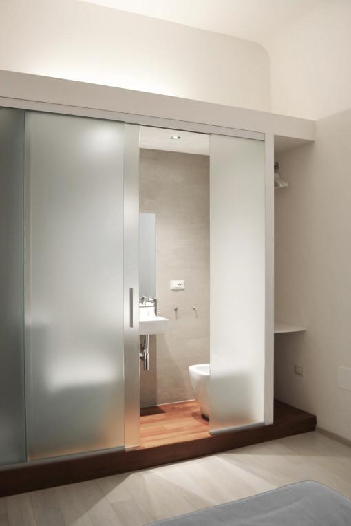 Nella camera Tubox un volume architettonico multifunzione ospita bagno, doccia e armadio.